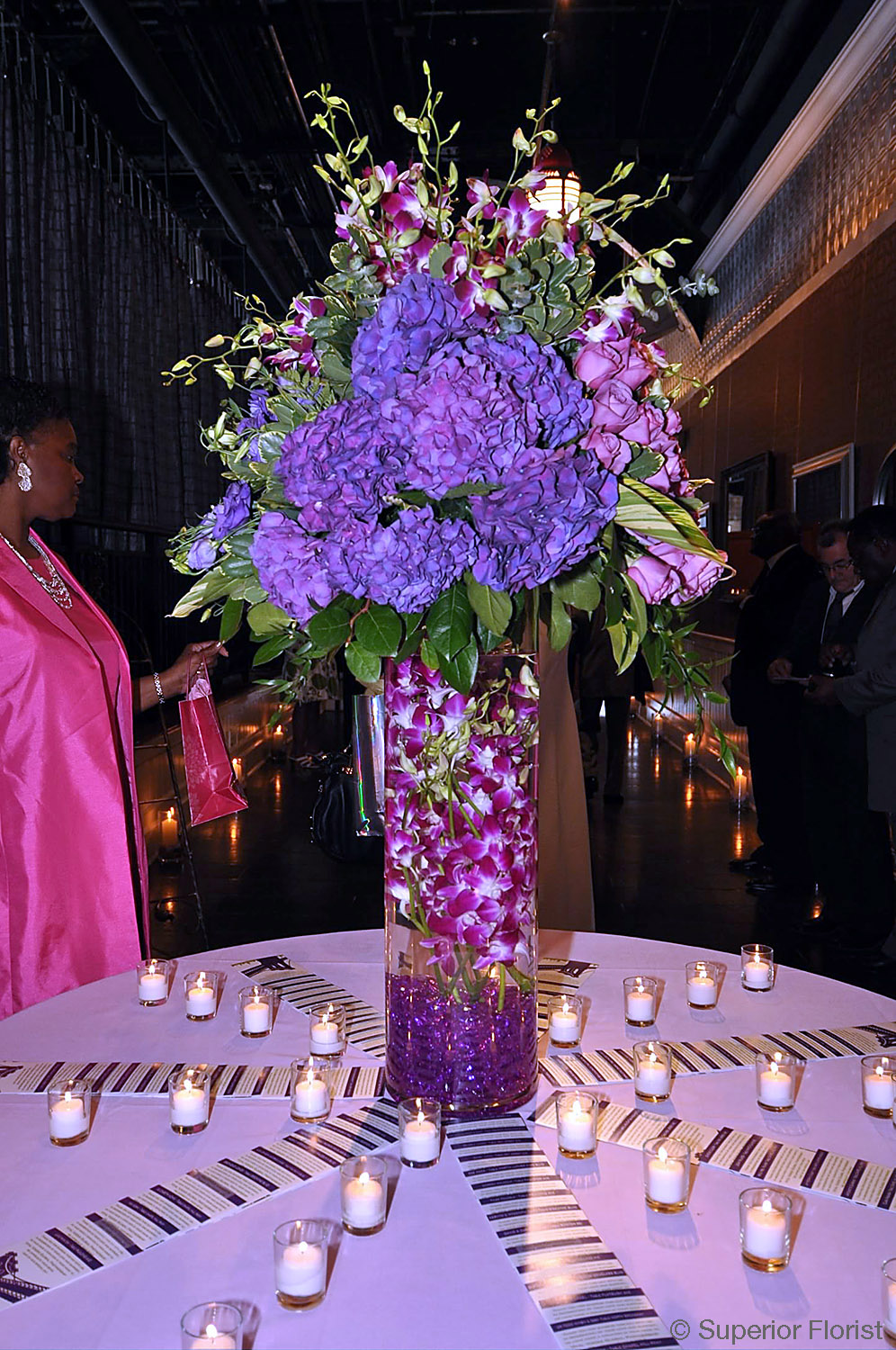 Superior Florist – Weddings – Escort Tables: Submerged, variegated Dendrobium orchids. Entire arrangement composed of quadrants of flowers (purple Hydrangeas in front, purple roses on right side, purple Lisianthus on left side, variegated Dendrobiums in rear). Vase: Tall, glass cylinder with purple gems at base.