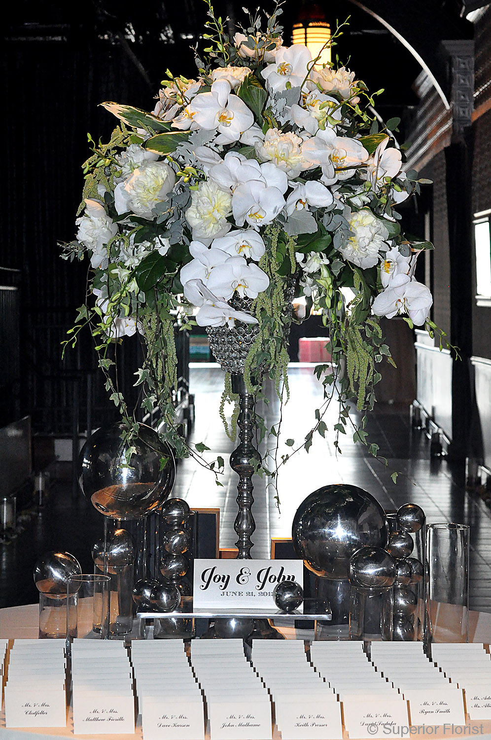 Superior Florist – Weddings – Escort Tables: White and green Phalaenopsis orchids, hanging Amaranthus and white Peonies arranged in a tall, silver and crystal vase.