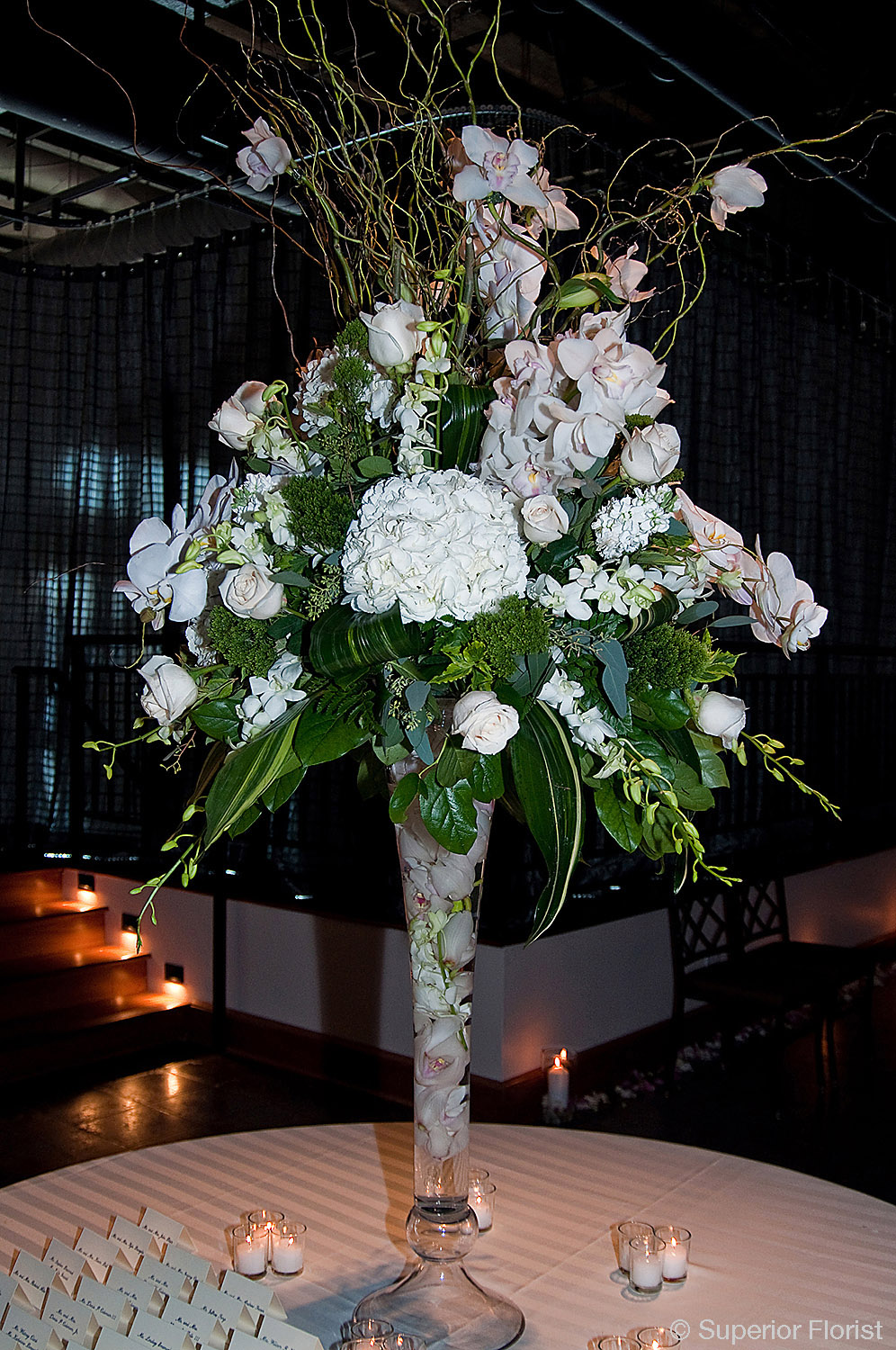 Superior Florist – Weddings – Escort Tables: Large bouquet of curly willows, Hydrangeas and Dendrobiums in a clear glass fluted vase with submerged Cymbidium orchids. The Lighthouse at Chelsea Piers, NYC.