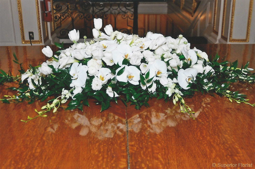 Superior Florist – Weddings – Escort Tables: Oblong arrangement of Dendrobium, Phalaenopsis and white tulips.