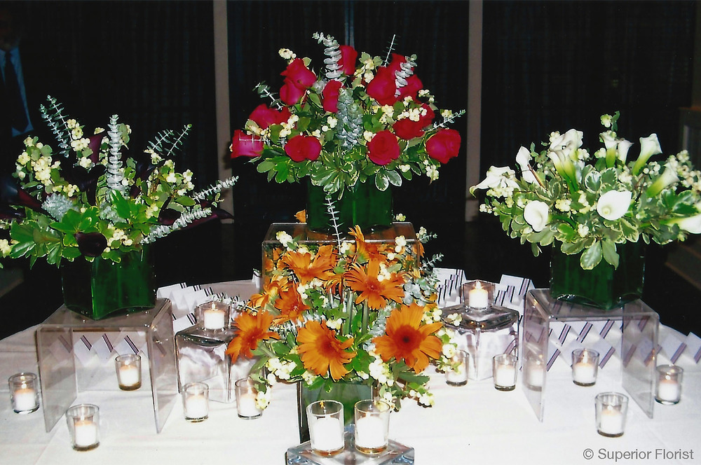 Superior Florist – Weddings – Escort Tables: Collection of cube vases with arrangements in assorted colors.
