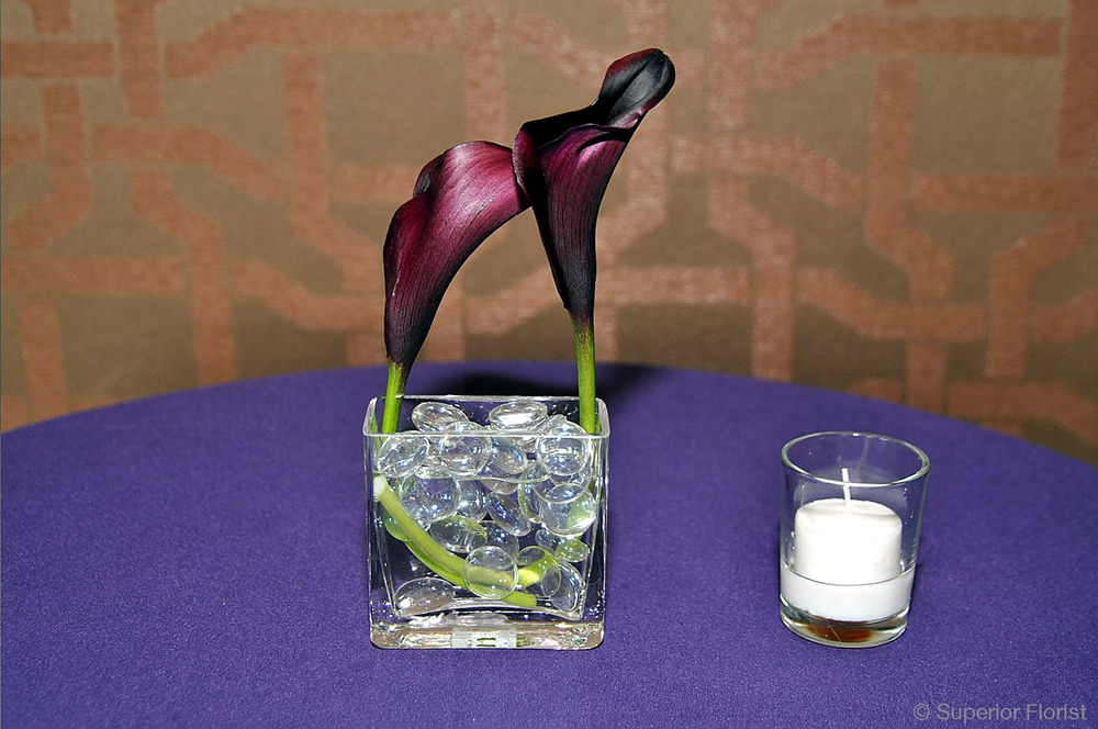 Superior Florist – Cocktail Tables: Floral arrangement of two curved Callas with glass gems in a small, glass cube vase.