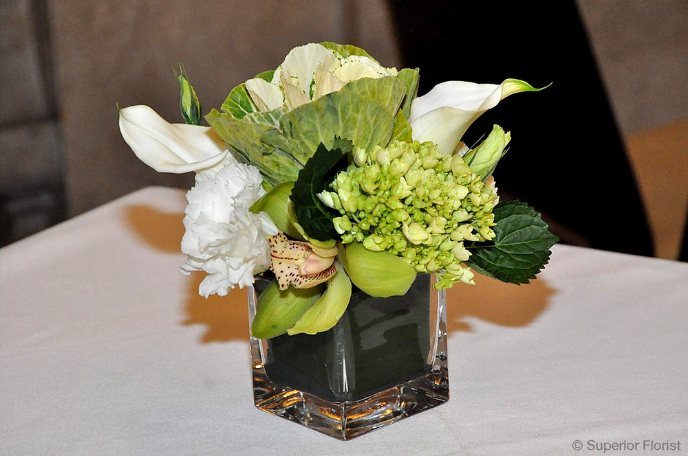 Superior Florist – Cocktail Tables: Floral arrangement of Cymbidium, Lisianthus, kale and Callas in a small, glass cube vase. Leaf wrap lining inside of vase.