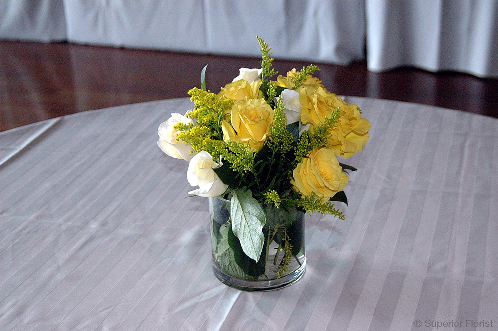 Superior Florist – Cocktail Tables: Floral arrangement of white and yellow roses and Solidago in cylindrical, glass vase.
