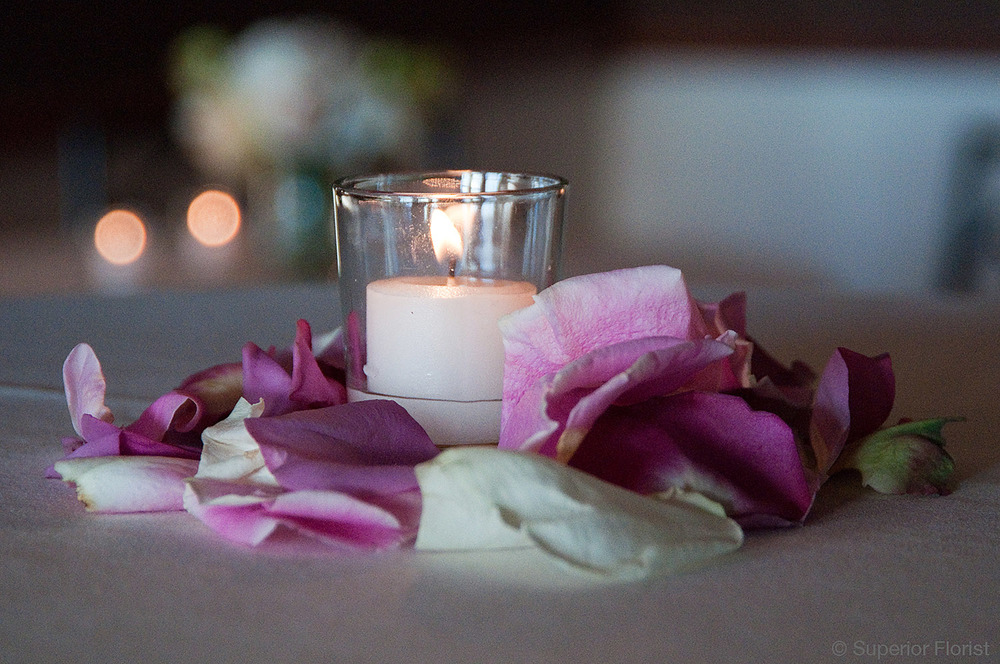 Superior Florist – Cocktail Tables: An elegant collection of rose petals surrounding a votive candle on a cocktail table.