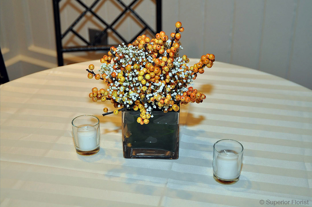 Superior Florist – Cocktail Tables: Floral arrangement of Baby's Breath and orange Ilex berries in small, glass cube vase.