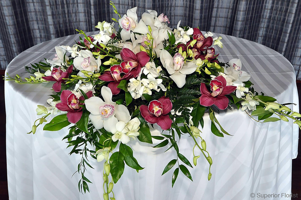 Superior Florist – Sweetheart Tables: Arrangement of cascading Cymbidiums and Italian Ruscus.