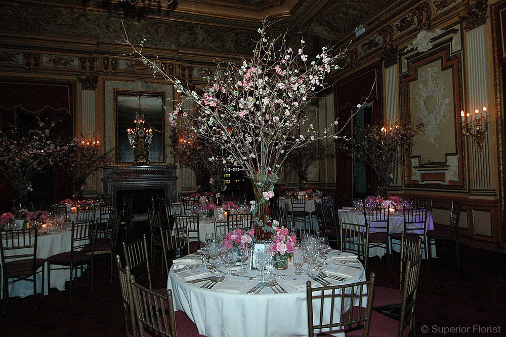 Superior Florist – Centerpieces:  Open quinces in a fluted vase surrounded by small vases of roses. The Metropolitan Club, NYC.