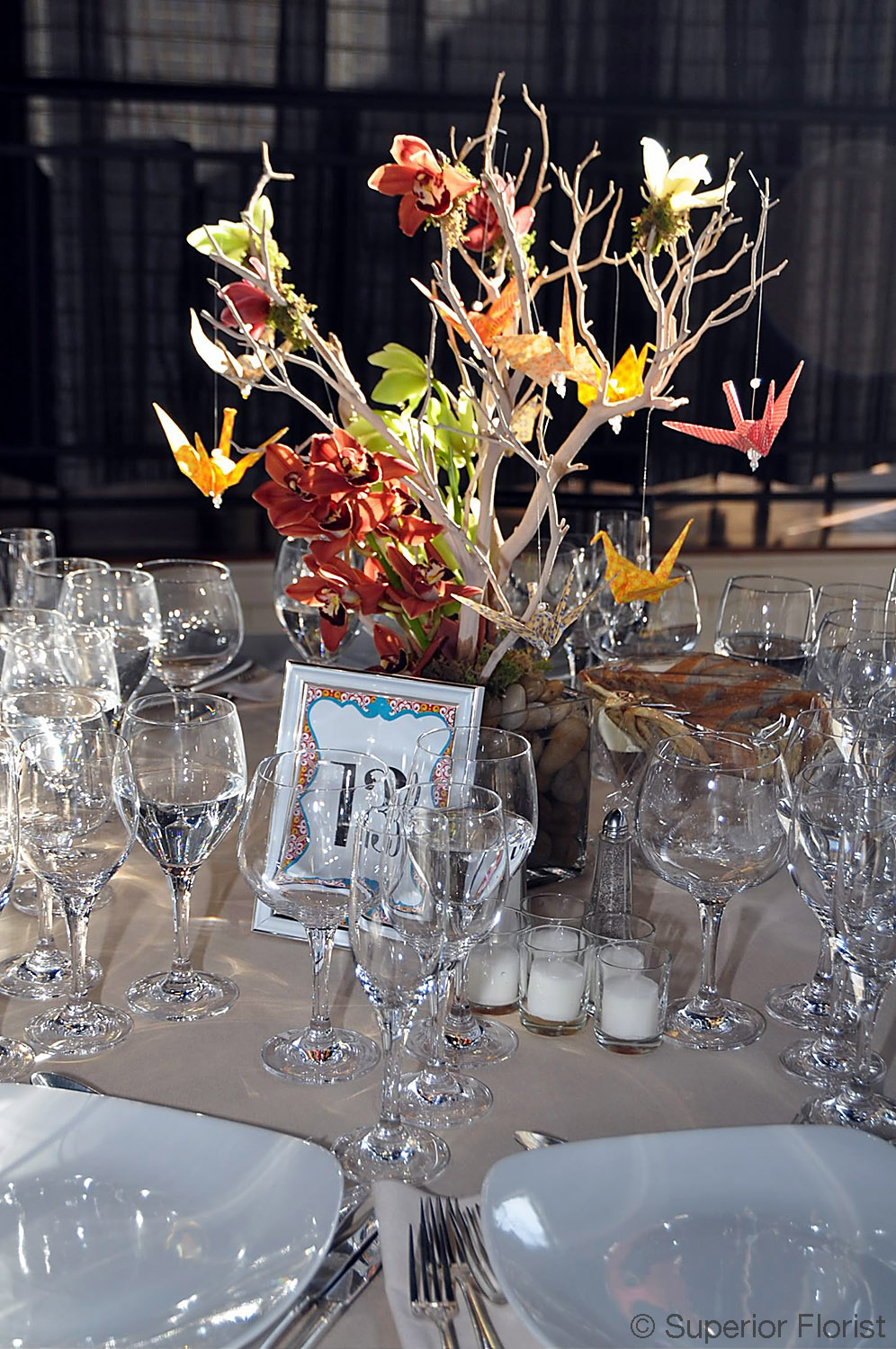 Superior Florist – Centerpieces:  Manzanita branches, miniature Cymbidiums, hanging votive candles and origami cranes (made by the bride). River rocks in bottom of glass cube vase.