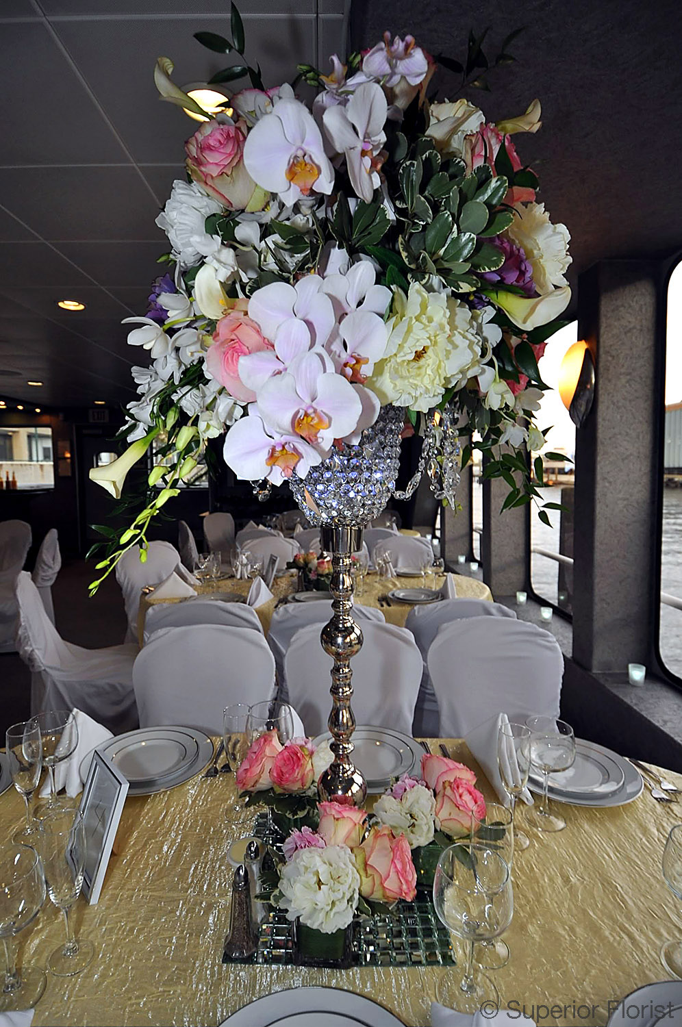 Superior Florist – Centerpieces: Phalaenopsis, Callas, Esperanzas, roses in a silver and crystal vase. Complimentary flowers on table at base of vase.