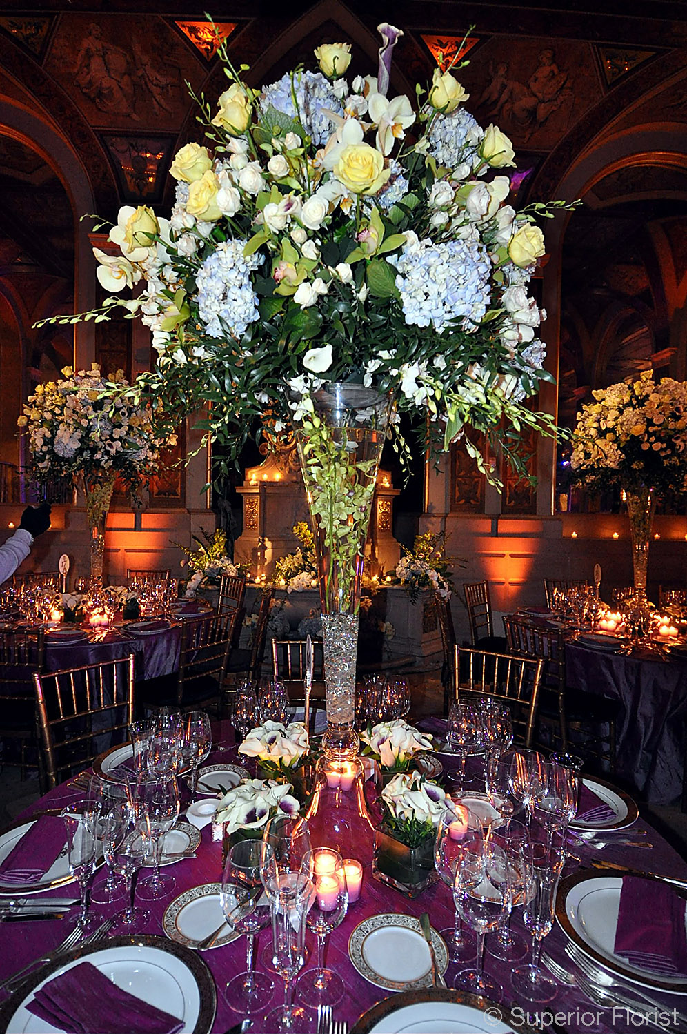 Superior Florist – Centerpieces:  An extravagant dinner table centerpiece atop a forty-inch tall glass vase. The Plaza Hotel, NYC.