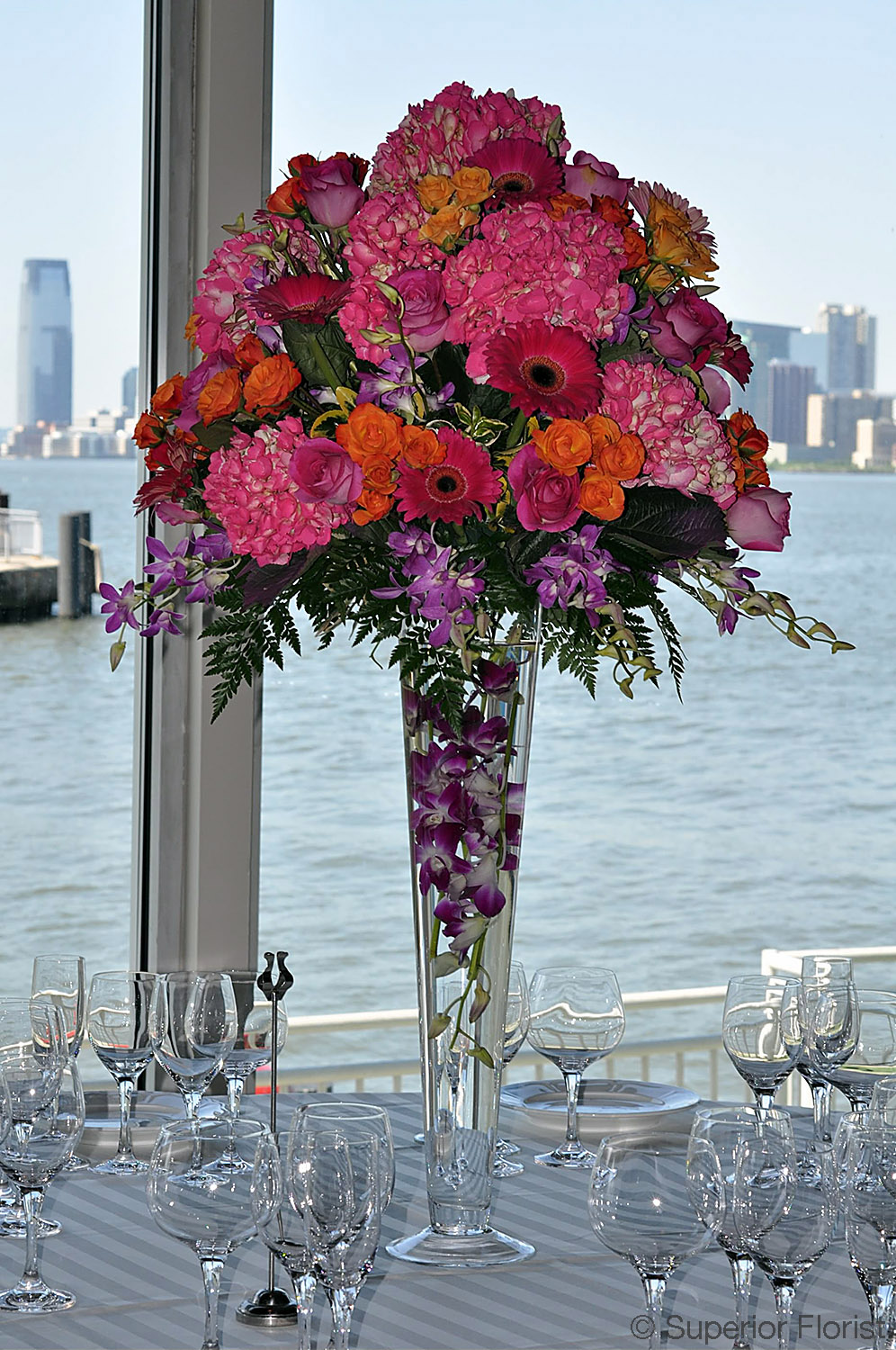 Superior Florist – Centerpieces:  Pink Hydrangeas, Gerberas and orange spray roses in a trumpet vase. Submerged Dendrobiums in vase.