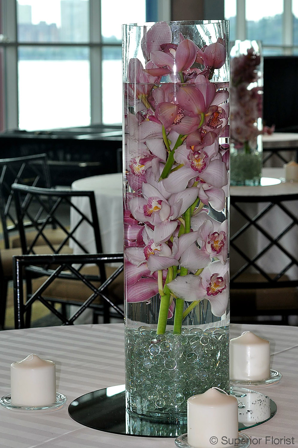 Superior Florist – Centerpieces: Submerged Cymbidiums in a glass cylinder vase with glass gems at bottom. Vase placed on mirror surrounded by three candles.
