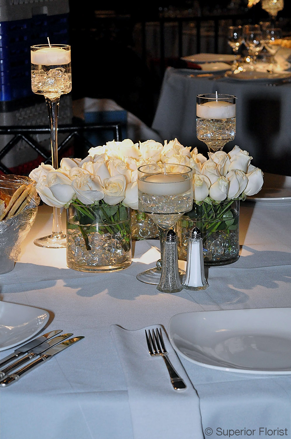 Superior Florist – Centerpieces:  Group of three, glass cylinder vases of white roses. Vases matched with three candleholders each with a floating candle.