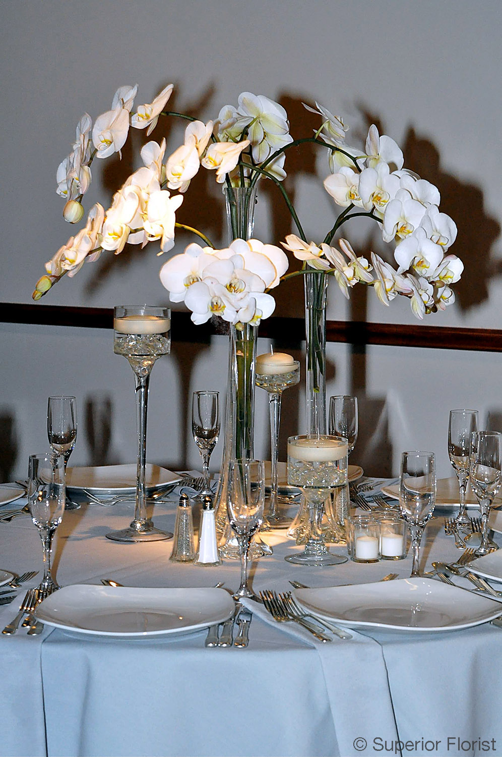Superior Florist – Centerpieces:  Three tower glass vases with cascading Phalaenopsis orchids, candleholders with floating candles.