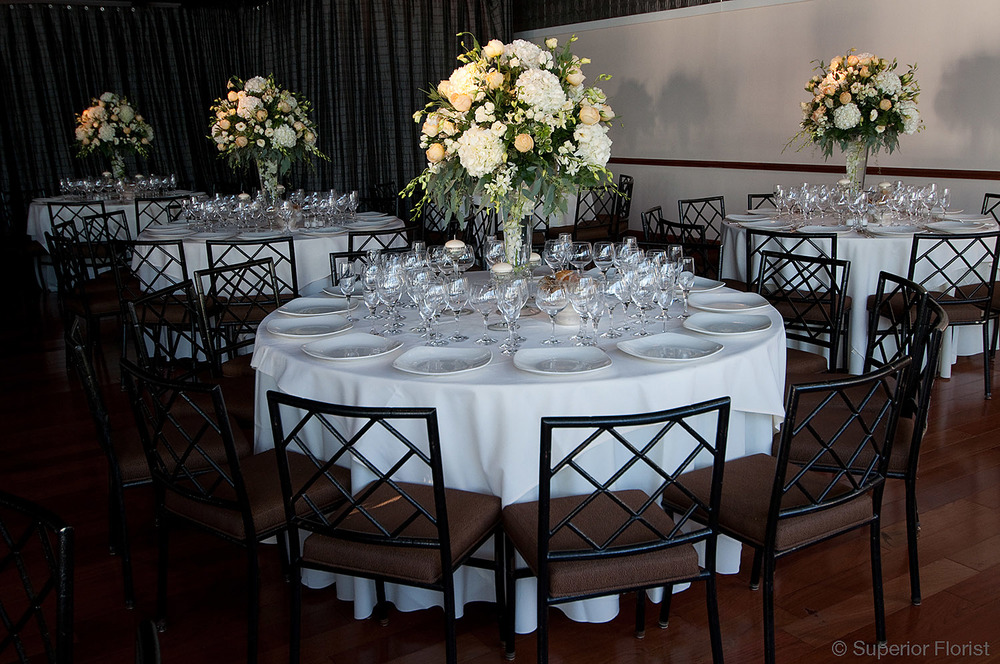 Superior Florist – Centerpieces:  Tables with tall arrangements of all white flowers and foliage. Upper tier of The Lighthouse at Chelsea Piers, NYC.