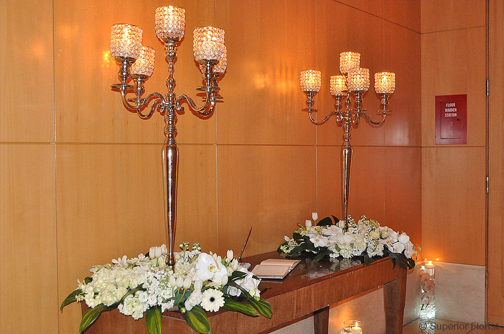 Superior Florist – Wedding Décor:  Sign-in table for guests on table with two candelabra and floral arrangements. The Four Seasons Hotel, NYC.