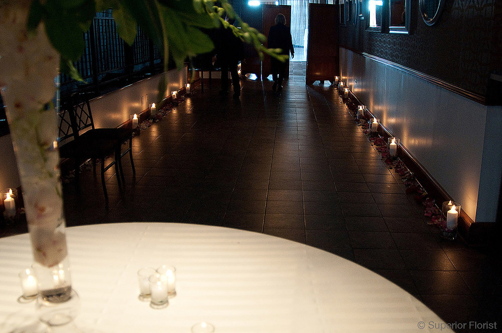 Superior Florist – Wedding Décor:  Pillar candles in glass vases in the entryway of The Lighthouse at Chelsea Piers, NYC.