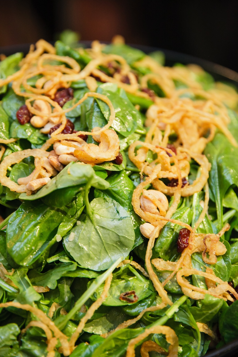 Organic Watercress, Spinach, and Arugula Salad with Dried Cherries and Cashews tossed in a Anjou Pear Vinaigrette and garnished with Sweet Crispy Onions | Red Sparrow Photography