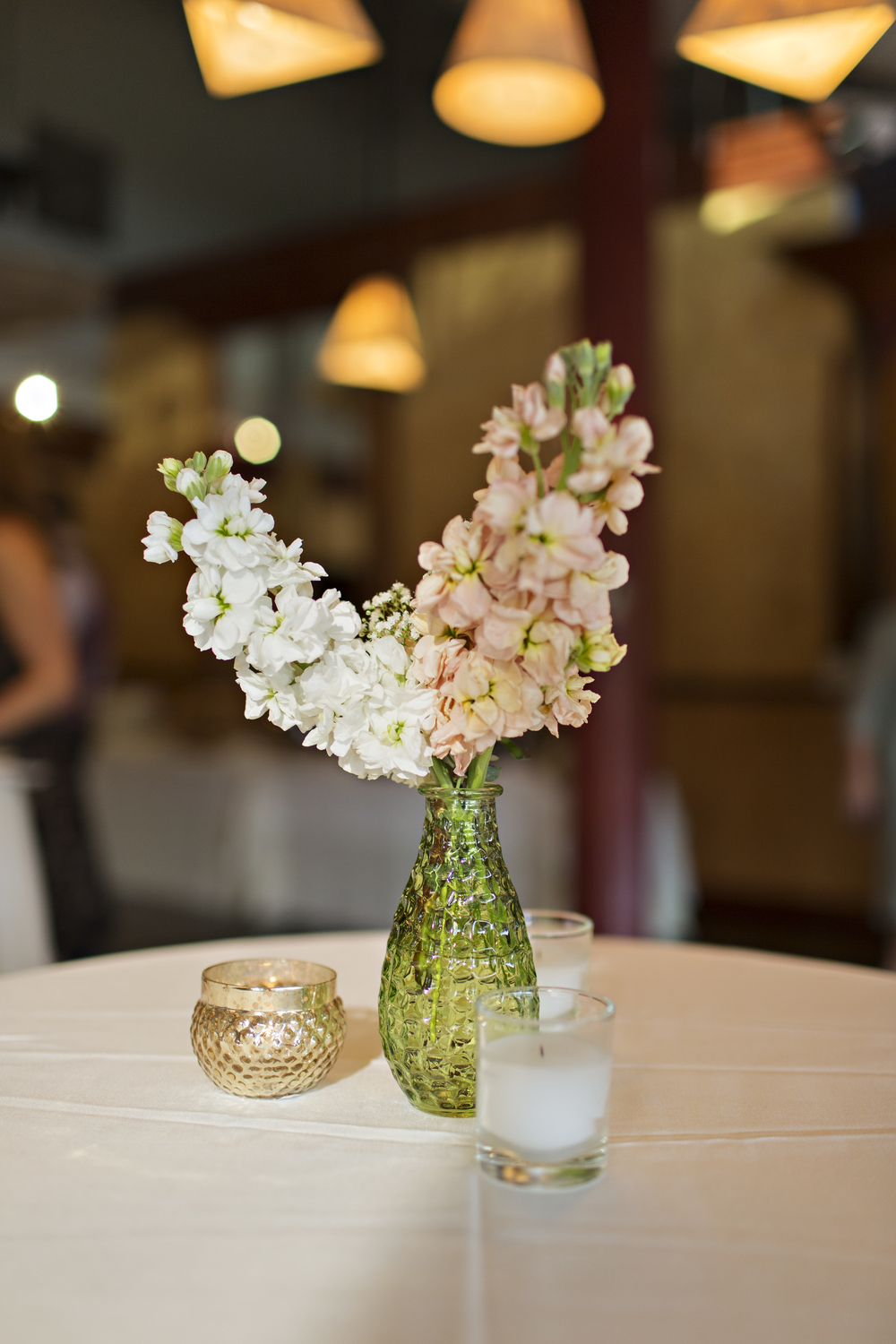Peach and white flowers in a textured green vase