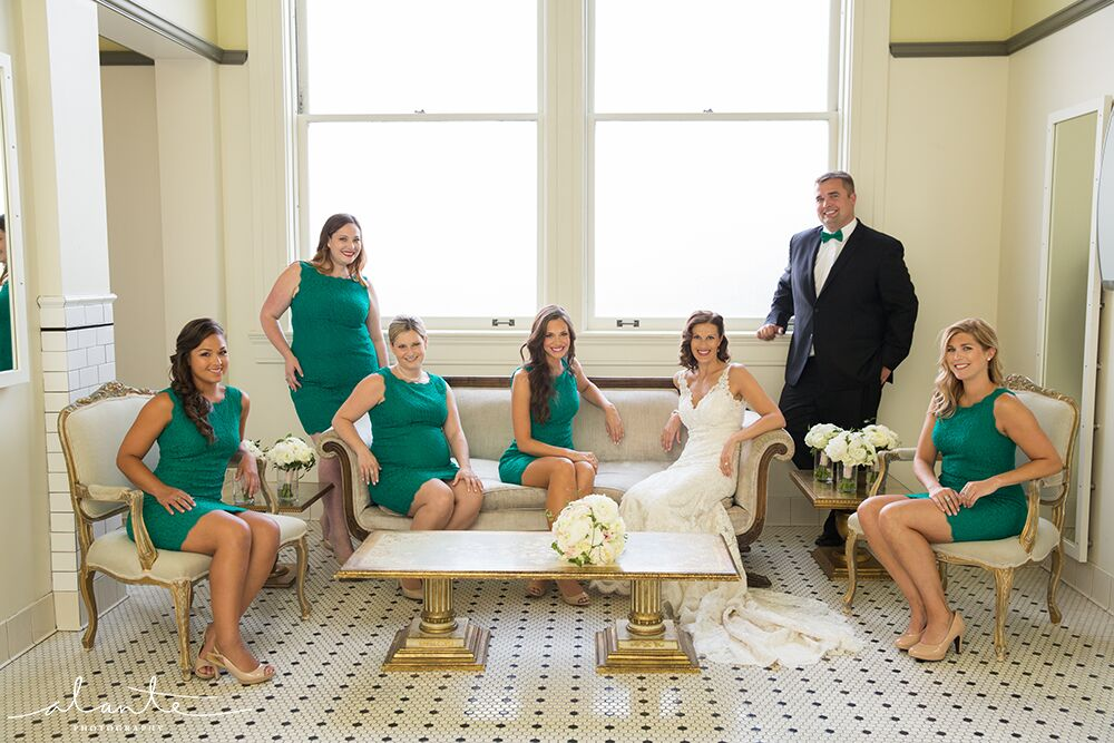 Bride and bridesmaids (and one bridesman!) pose on vintage furniture at the Great Hall