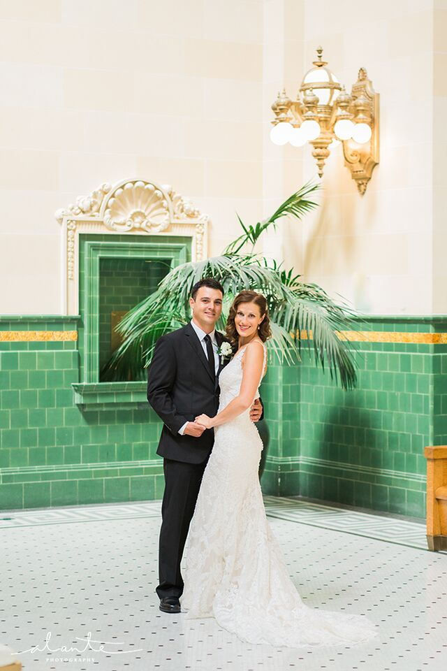Bride and groom in front of the emerald backdrop at the Great Hall