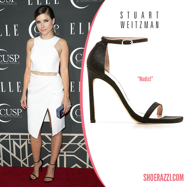 Credit: FayesVision/Wenn   Sophia Bush  wore  Stuart Weitzman   Nudist  sandals to the 2014 Elle Women in Music Celebration held in Hollywood. They feature  black silk satin , 4.5″ heel and thin adjustable ankle strap.  Nudist  is available in several styles at  Stuart Weitzman  and gypsum or black leather at  Shopbop .  She was the best-dressed wearing a Camilla and Marc white snake-printed leather  Cypress  box cropped leather top and   First Encounter  asymmetrical wrap skirt  from the  Fall 2013 collection .  Sophia wore her hair back in a side-parted low ponytail before finishing with a glossy nude lip, dramatic under-eye liner and coral nails. She also added a   Bowie  diamond ring  and  rainbow diamond earrings  by AS29 jewelry. Other accessories included a Rauwolf emerald cut   Gemstone  plexiglass clutch .