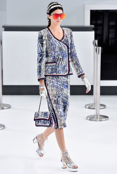 Another day, another runway win for Kendall Jenner. Or, make that a double win. The reality star slash model starred in Karl Lagerfeld's latest production, in which he transformed the Grand Palais into a Chanel-branded airport terminal, complete with check-in counters, a baggage drop-off, and stewardesses. And as a stylish jet-setting pro IRL, Jenner played her role in the Chanel spring 2016 show to perfection. First she breezed through the concourse in a trimmed tweed ladylike skirt set—modernized with an onslaught of futuristic accessories, including silver headbands, cool orange shades, metallic silver moto gloves, and see-through lace-up platform booties (above).