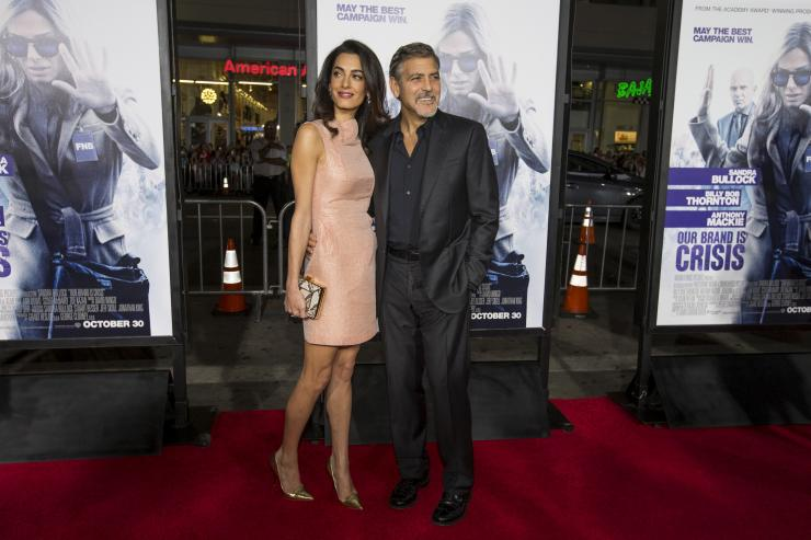 "Producer George Clooney and his wife Amal pose at the premiere of ""Our Brand Is Crisis"" in Hollywood, California October 26, 2015. The movie opens in the U.S. on October 30. REUTERS/Mario Anzuoni"