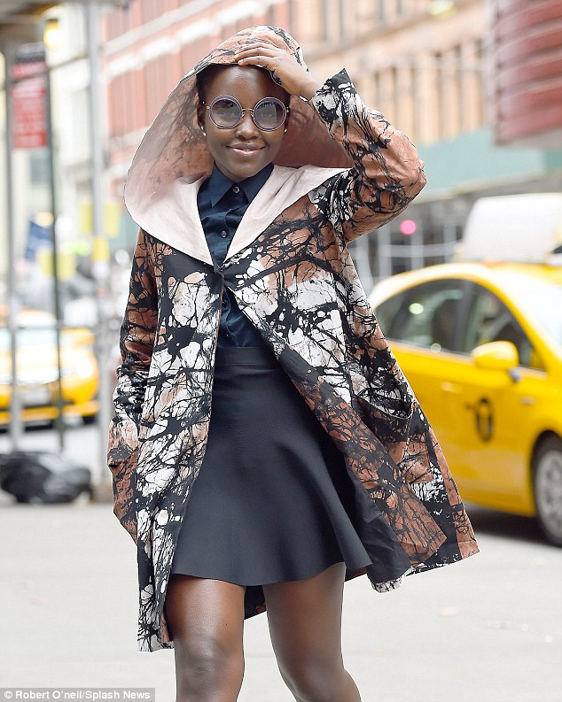Chic: Actress Lupita Nyong'o wore a stylish hooded cape with a black paint-splattered pattern while on her way to a matinee performance of her play Eclipsed in Manhattan on Saturday    Read more:  http://www.dailymail.co.uk/tvshowbiz/article-3308651/All-world-s-stage-Lupita-Nyong-o-wears-hooded-jacket-black-mini-skirt-heads-Broadway.html#ixzz3r4tAI8hf   Follow us:  @MailOnline on Twitter  |  DailyMail on Facebook