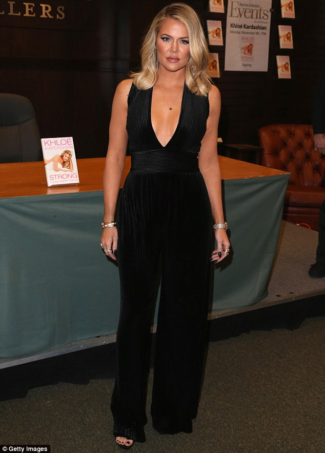 Stunner: Khloe Kardashian donned a sleeveless black jumpsuit for her book signing on Monday in Los Angeles     All smiles: The reality star revealed her cleavage in the low-cut number to promote her book, Strong Looks Better Naked, which was released on November 3rd  Her evening outfit featured vertical lines for the top and bottom half of the piece, with horizontal markings over the waist.   The long jumpsuit only allowed a small peek at the E! star's heels.  Khloe wore her short golden locks with a deep side part and a slight curl.