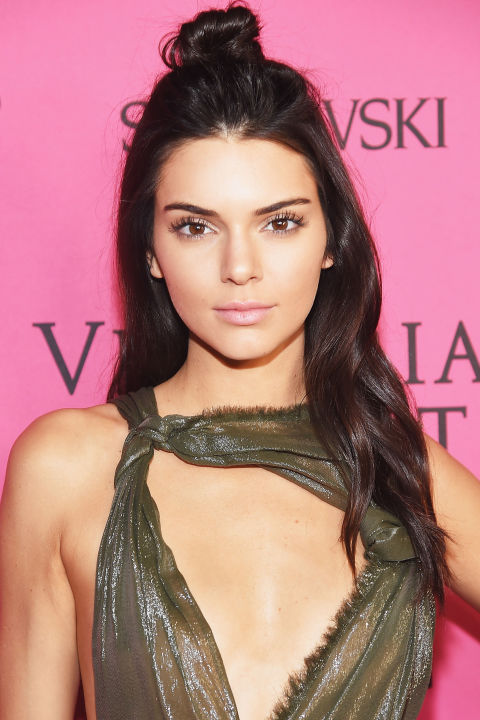 Who: Kendall Jenner  What: A Half Knot  How-To: The model stepped off her first Victoria's Secret runway and onto the pink carpet at the afterparty, but not before remixing her long waves into a more casual style. The high bun draws the attention up toward her ultralong lashes and highlighted lids, so nothing more than lip balm is required.  Editor's Pick: Estée LauderSumptuous Infinite Daring Length + Volume Mascara, $26, esteelauder.com .  GETTY