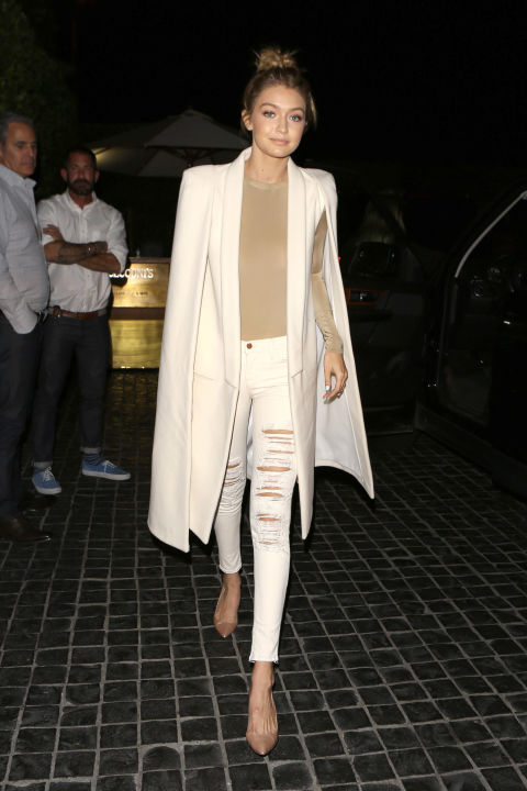 For a dinner date with the Kardashians in L.A., the model steps out in a white Olcay Gulsen coat paired with distressed denim, a nude bodysuit and matching heels. AKM-GSI