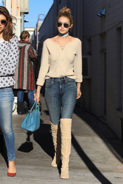 In a lace-up sweater, jeans, over-the-knee suede boots and a '90s-inspired choker that you can  DIY here .  GETTY