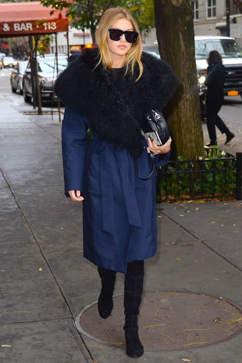 The model bundles up while in New York wearing a navy fur collared Kempner coat and accessorizing the look with Karen Walker sunnies.