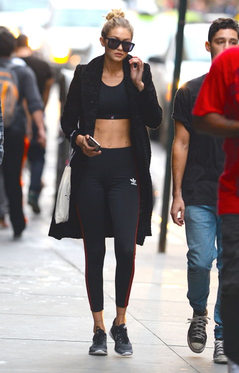 Hadid wears a Sweaty Betty bra and Adidas leggings paired with a long winter coat while out and about in New York.  GETTY