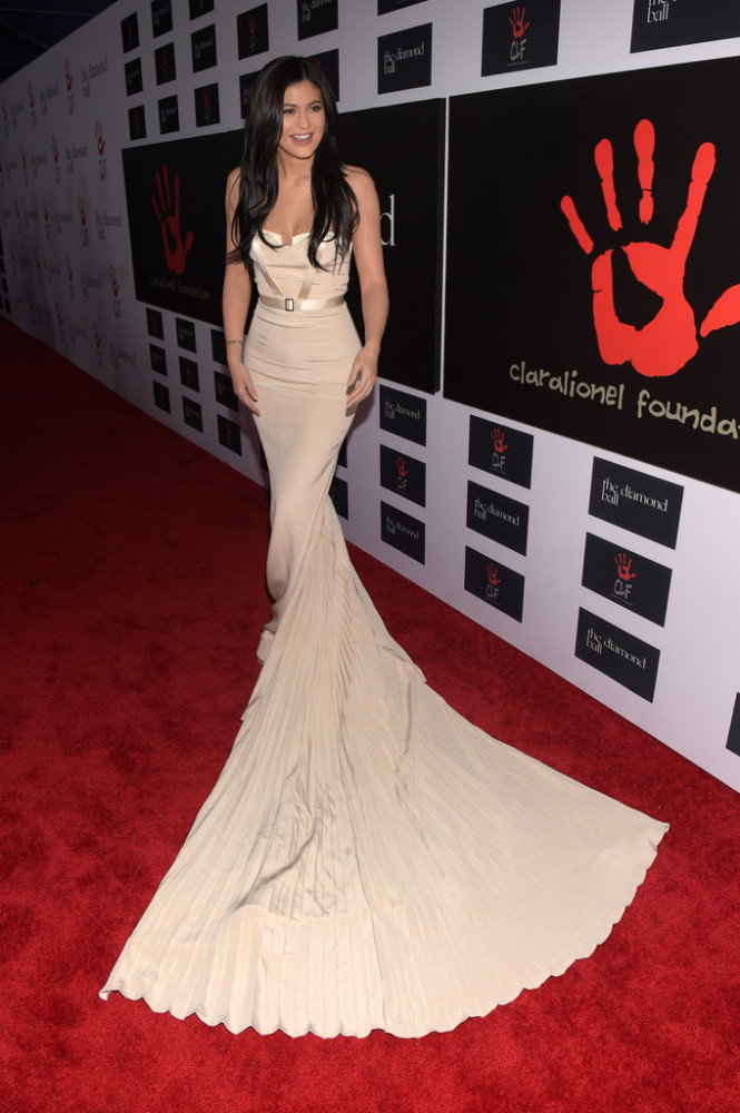 Kylie Jenner showed off her pearly whites in a cream gown with a waist-cinching belt.