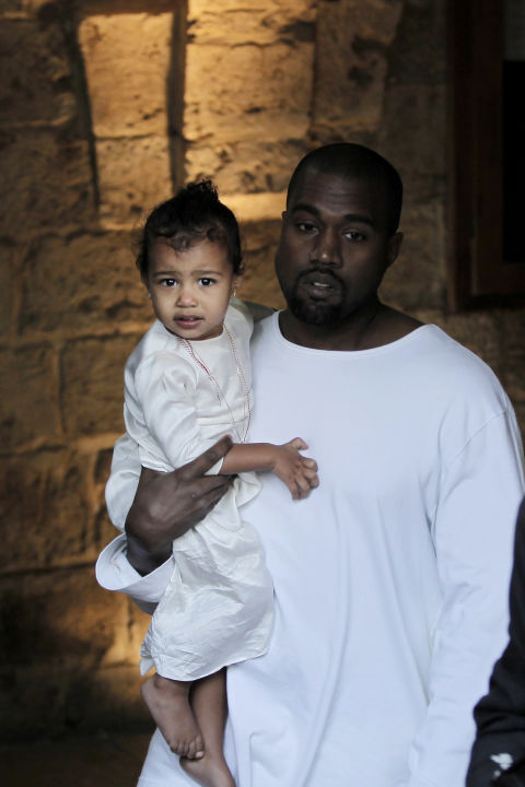 North wears a white satin dress layered with thin necklaces for her baptism ceremony in Jerusalem.