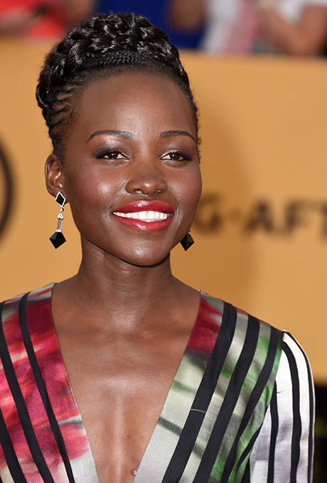 Lupita Nyong'o  A great way to complement red lipstick? Go for deep plum-hues on the eye like Lupita did.