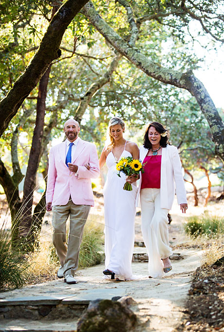 A wine-meets-surfboard wedding like the one held by Besse and Michael calls for laid-back, breezy attire. Besse's mother selected a casual white pantsuit that she spiced up with a magenta shell, decorative necklace, and a flower in her hair. Her mom has a history of good wedding style: Besse wore a shortened version of her mother's wedding dress, which was purchased from  Saks Fifth Avenue  in 1979, for the wedding reception.    See more white mother-of-the-bride attire.      View more photos from Besse and Michael's wedding.    Photo:  Noah Hawthorne Photography