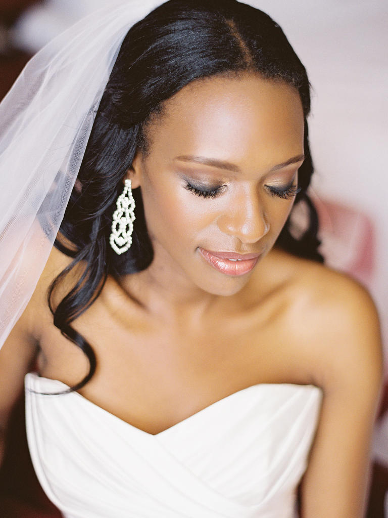 PHOTO BY VICKI GRAFTON PHOTOGRAPHY  Strobing (the latest highlighting technique) makes her face glow— and  shows off her amazing cheekbones. A lightened-up version of a smoky eye and shimmery peach lip gloss finish off this elegant look.  From the album  A Bright Summer Wedding in Fort Belvoir, VA