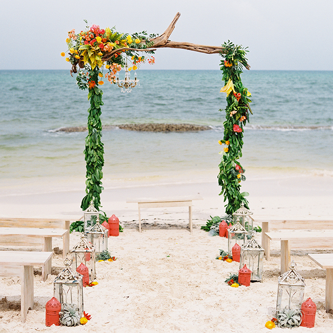 A driftwood arbor is adorned with fresh tropical flowers and greenery for summery, seaside nuptials.  Photo:  Lane Dittoe