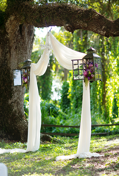Rustic gets whimsical with this wedding altar consisting of draped fabric, lanterns filled with rich blooms, and a crystal chandelier, all nestled within a tree's sturdy branches.  Photo: Stacy Sullivan of  Set Free Photography