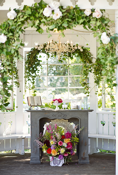 A fireplace wedding altar gets gussied up with whimsical florals, an arch of cascading greenery, and a vintage chandelier, designed by  Danner and Soli .  Photo:  Erica Ann Photography