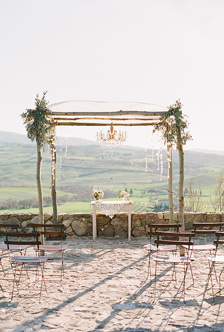 A rustic wooden chuppah, with a scalloped lace canopy and gold and crystal chandelier, overlooks the hills of Tuscany.  Photo:  Jose Villa