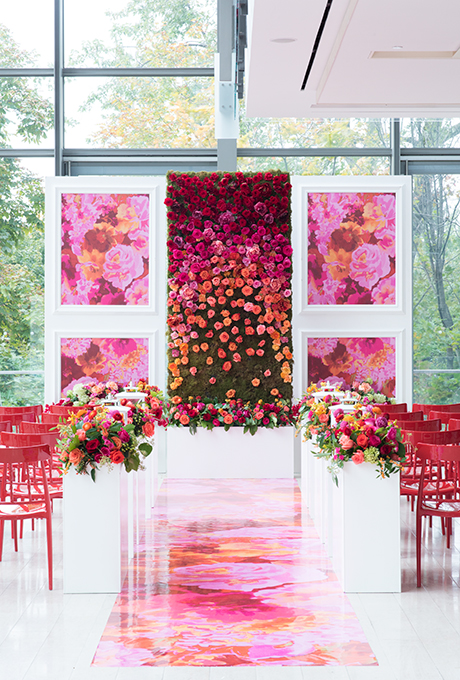 Colorful ceremony altar with rose-covered flower wall and illustrated panels, created by  Laura & Co Events .  Photo:  5ive15ifteen Photo Company