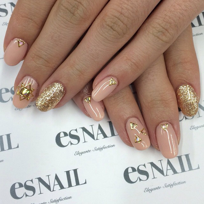 A pink manicure with gold decals and sparkle.  Photo: es Nail via  Instagram