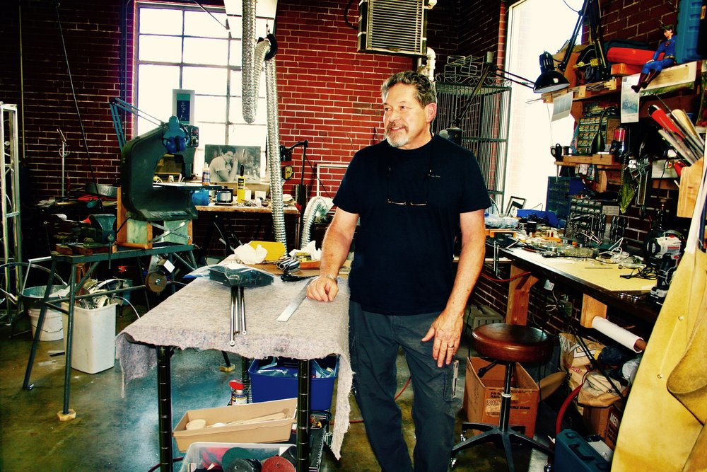 Portrait of Gary Justis standing by one of his working tables as a photograph by the window from long ago looks on. Photography by Menendez.
