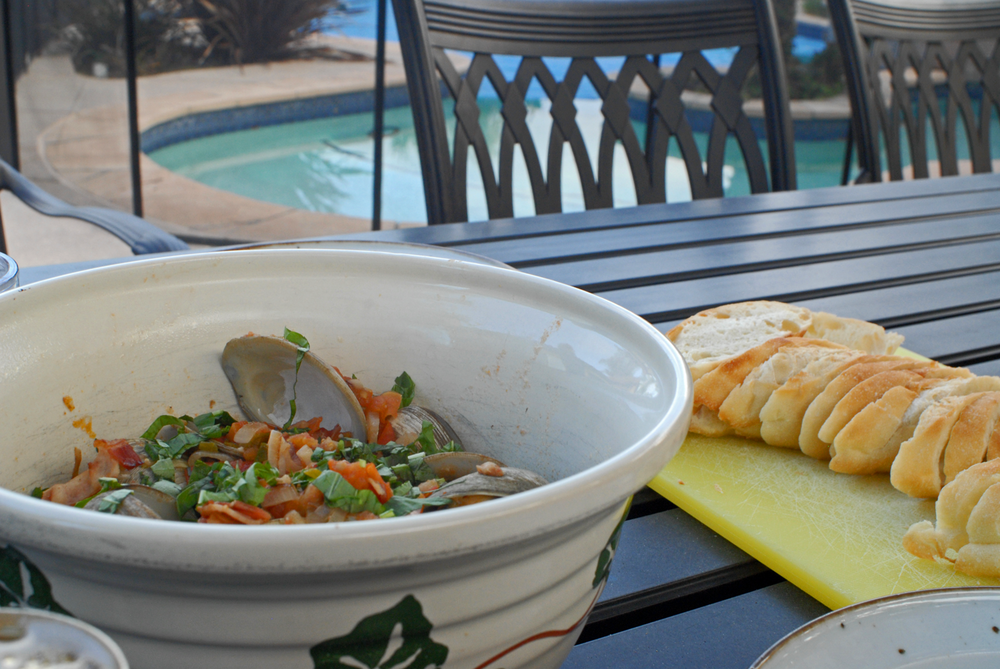 bowl-of-clams-on-table-with-bread-by-pool.png