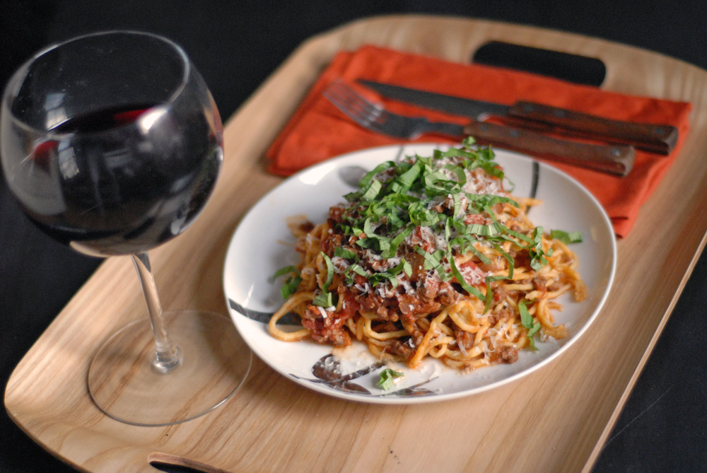 spaghetti-with-meat-sauce-on-a-tray-with-a-glass-of-red-wine.png